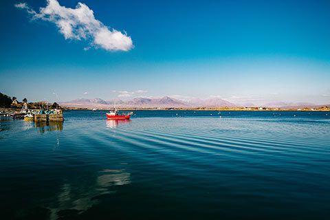 Bateau de pêche rentrant dans le port d'un village irlandais