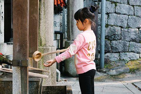 Une enfant réalisant le rituel de l'eau