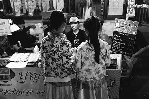 Photo de rue de Chiang Mai montrant deux jeunes filles à un stand